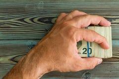 Укомплектуйте личным составом держать сложенную валюшку банкнот 20 долларов стоковое изображение rf