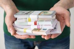 Укомплектуйте личным составом держать стога евро и долларов в его руках Стоковое фото RF