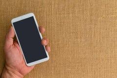 Укомплектуйте личным составом держать умный телефон над предпосылкой мешковины стоковые фото