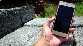 Укомплектуйте личным составом держать Smartphone в руке и показывать ему лицевую сторону ` s Стоковая Фотография