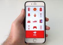 Укомплектуйте личным составом держать smartphone с apps покупок JD китайскими онлайн Стоковое фото RF