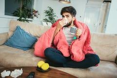 Укомплектуйте личным составом дуть его нос пока лежа больной дома стоковые фото