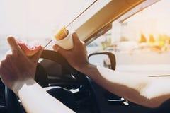 Укомплектуйте личным составом еду donuts и картофельной стружки пока управляющ автомобильным multitaski Стоковые Изображения
