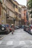 Укомплектуйте личным составом ехать велосипед с его сыном на дороге против домов и узкой улицы в болонья, Италии Стоковое Фото