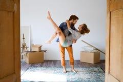 Укомплектуйте личным составом женщину нося в его оружии, двигая в новый дом Стоковые Фото