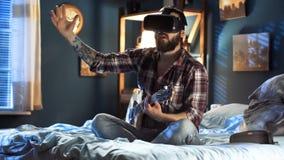Укомплектуйте личным составом играть гитару в стеклах VR на кровати на ноче стоковое изображение