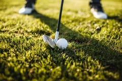Укомплектуйте личным составом играть гольф на поле для гольфа в солнце Стоковые Фотографии RF