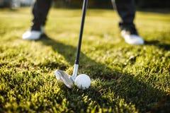 Укомплектуйте личным составом играть гольф на поле для гольфа в солнце Стоковая Фотография RF