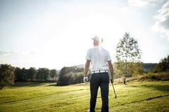 Укомплектуйте личным составом играть гольф на поле для гольфа в солнце Стоковое Изображение