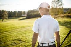 Укомплектуйте личным составом играть гольф на поле для гольфа в солнце Стоковые Изображения RF