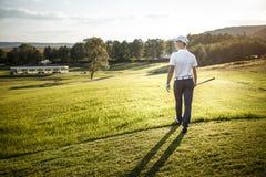 Укомплектуйте личным составом играть гольф на поле для гольфа в солнце Стоковое Изображение RF