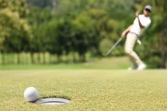Укомплектуйте личным составом игрока в гольф веселя после шара для игры в гольф на зеленом цвете стоковое изображение rf