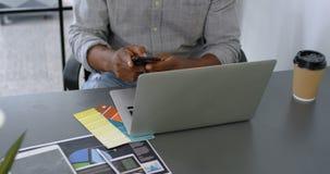 Укомплектуйте личным составом иметь кофе пока использующ мобильный телефон на столе 4k видеоматериал
