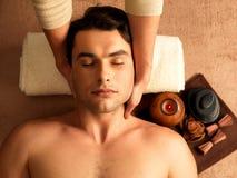 Укомплектуйте личным составом иметь массаж шеи в салоне спы Стоковое фото RF