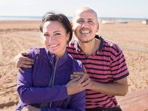Укомплектуйте личным составом и средн-постаретая женщина сидя на пляже стоковое изображение rf