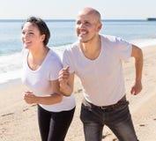 Укомплектуйте личным составом и средн-постаретая женщина сидя на пляже стоковое изображение