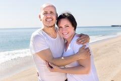 Укомплектуйте личным составом и средн-постаретая женщина сидя на пляже стоковые фото