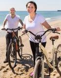 Укомплектуйте личным составом и средн-постаретая женщина сидя на пляже стоковые изображения