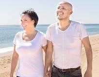 Укомплектуйте личным составом и средн-постаретая женщина сидя на пляже стоковое фото rf
