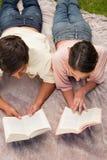 Укомплектуйте личным составом и чтение женщины пока лежащ на одеяле Стоковые Изображения