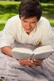 Укомплектуйте личным составом книгу чтения пока он лежит на одеяле Стоковая Фотография RF