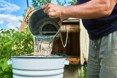 Укомплектуйте личным составом лить воду как раз занятую от хорошо в покрытое эмалью ведро стоковое изображение rf