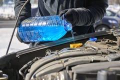 Укомплектуйте личным составом лить жидкость антифриза в танке шайбы лобового стекла автомобиля стоковая фотография rf