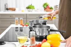Укомплектуйте личным составом лить пищевое масло от бутылки в кастрюльку стоковое изображение rf
