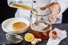 Укомплектуйте личным составом лить чай kombucha в опарник стоковые фото