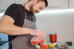 Укомплектуйте личным составом лить smoothie от blender в опарнике стоковые фото