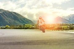 Укомплектуйте личным составом мотоцикл катания на шоссе против сцены горы Стоковые Изображения