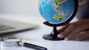Укомплектуйте личным составом наблюдая глобус для того чтобы выбрать назначение отключения, бюро путешествий, летние каникулы стоковое фото rf