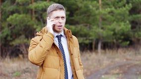 Укомплектуйте личным составом на заднем плане деревьев в рубашке куртки и свяжите бизнесмен говоря на телефоне в древесинах, рабо видеоматериал