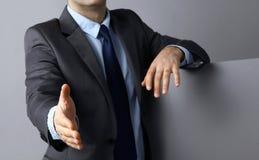 Укомплектуйте личным составом носить костюм предлагая трясти руки Стоковые Изображения
