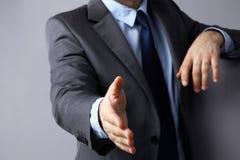 Укомплектуйте личным составом носить костюм предлагая трясти руки Стоковое Изображение