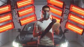 Укомплектуйте личным составом нося защитную маску и стекла держа полируя машину с красными теплыми светами в предпосылке сток-видео