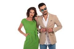 Укомплектуйте личным составом нося солнечные очки застегивая пальто пока женщина полагается на ем Стоковое Изображение RF