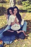 Укомплектуйте личным составом обнимать его беременную жену от задней части сидя на том основании Стоковое Фото