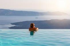 Укомплектуйте личным составом ослаблять в бассейне безграничности, смотря вид на море стоковые изображения