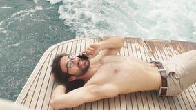Укомплектуйте личным составом ослаблять под солнцем, лежа на шлюпке на море Роскошные каникулы на яхте в островах сток-видео