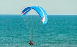 Укомплектуйте личным составом параглайдинг с морем голубого парашюта надводным, ясным небом Стоковое Изображение RF