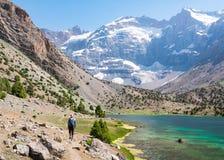 Укомплектуйте личным составом пеший туризм вокруг озер Kulikalon в горах Fann, Tajikis стоковые фотографии rf
