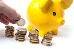 Укомплектуйте личным составом подсчитывать монетки евро в руке и на желтом piggy b Стоковое Изображение