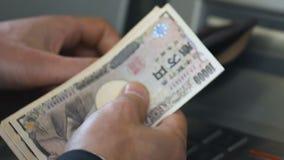 Укомплектуйте личным составом подсчитывать японские иены разделенные от ATM, кладя получите внутри бумажник наличными, конец-ввер акции видеоматериалы