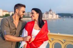 Укомплектуйте личным составом покрывать счастливую женщину при венгерский флаг смотря к каждому надгоризонтному Стоковые Фотографии RF