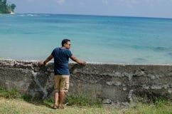 Укомплектуйте личным составом положение на пляже и смотреть море Стоковое Изображение RF