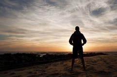 Укомплектуйте личным составом положение смотря заход солнца в пляже Стоковая Фотография RF