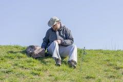 Укомплектуйте личным составом получать готовый удить от травянистых речного берега, усаживания и l Стоковое фото RF