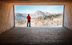 Укомплектуйте личным составом пребывание в большом деревянном ангаре и взгляды на снежных горах Стоковое Фото