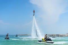 Укомплектуйте личным составом представлять на новом flyboard на карибском тропическом пляже положительно стоковые изображения rf